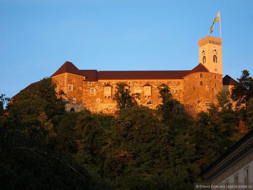 Освещенный закатом Люблянский замок (IX—XIX вв) расположен на высоком холме над старым городом. Оттуда открывается великолепный вид на весь город.