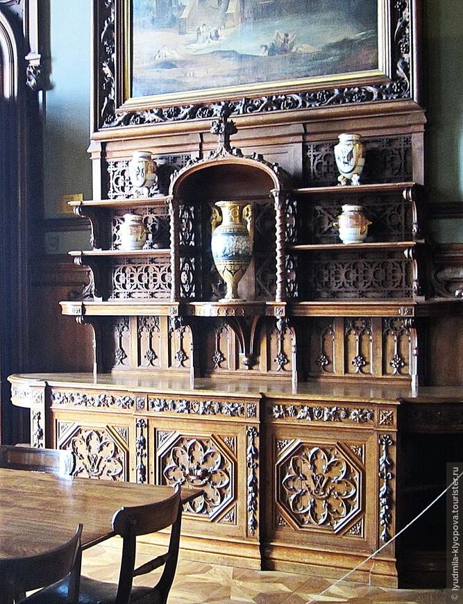 Интерьер парадной столовой стилизован под интерьер средневекового рыцарского замка. Здесь много резьбы по дереву – на панелях, на потолке, на мебели (здесь – буфет), на рамах, обрамляющих картины.