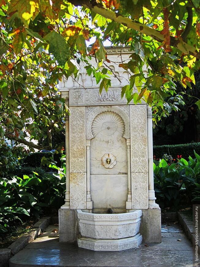 """В память о первом приезде в Ливадию царской семьи в парке в 1863 году был установлен мраморный фонтан. Он декорирован восточным орнаментом, а в верхней части фонтана арабскими буквами высечено: """"Ливадия"""". Из бронзовой головы барашка, вмонтированного в мраморную плиту, тонкой струйкой льётся вода."""
