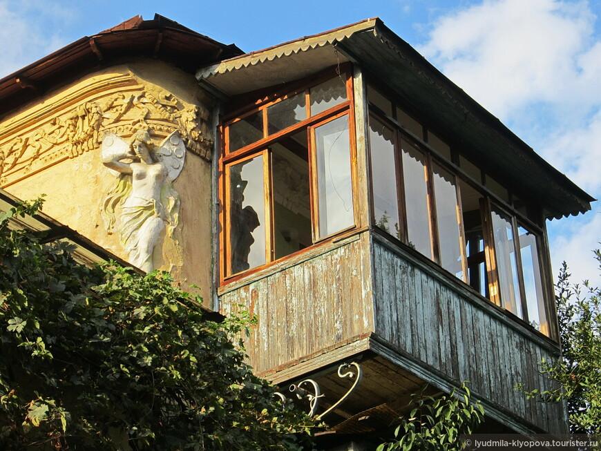 Лепной карниз по верху здания, фигурка, судя по всему, феи с крылышками бабочки – и тут же крытый балкончик, вносящий восточную нотку.