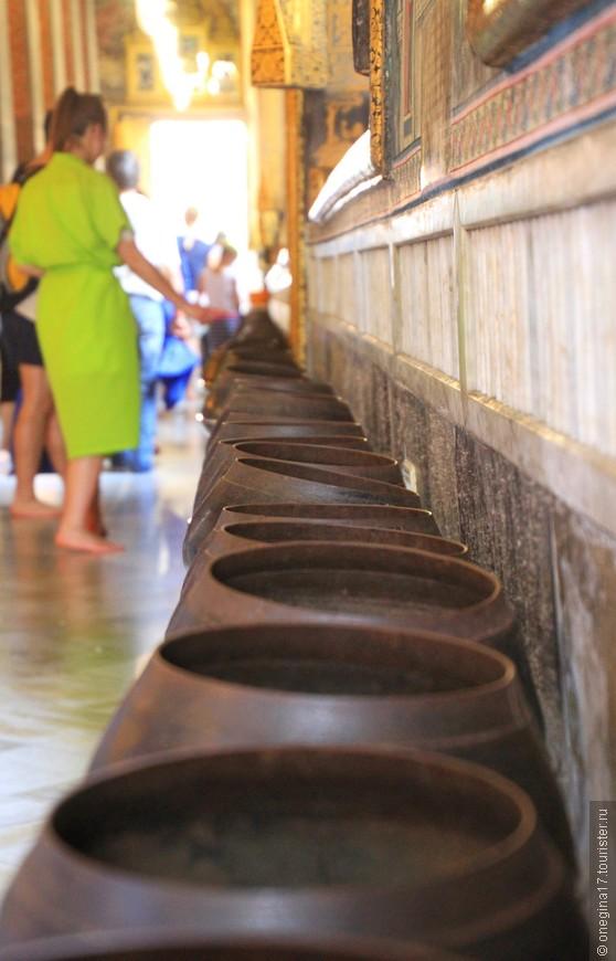 108 чаш, в которые надо бросать монетки (если хотите, конечно). Звон от монеток раздается непрерывно, очередь желающих очистить свою карму не прекращается и туристов в ней ничуть не меньше, чем тайцев.