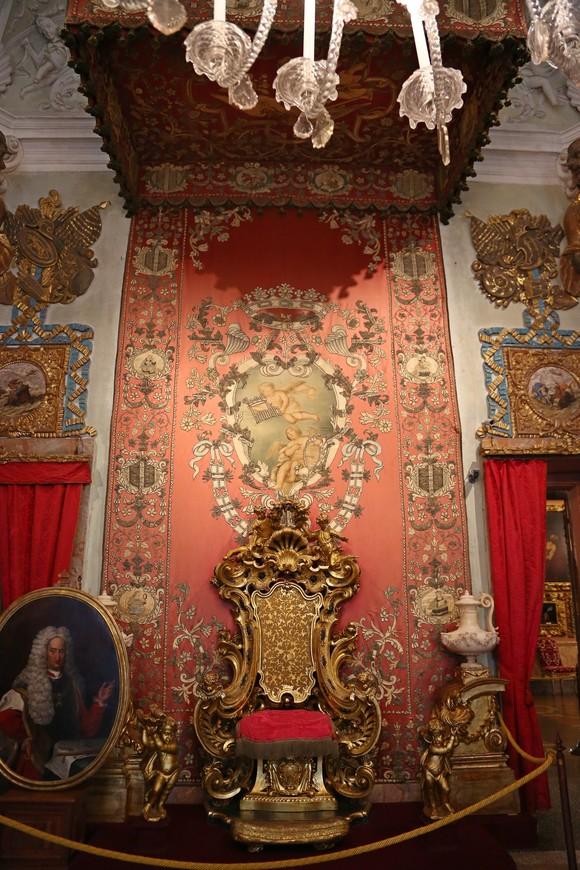 """Тронный зал поражает своей роскошью и обилием золотых деталей, зал выполнен в стиле барокко. Девиз семейства """"Смирение""""на ковре за спинкой трона, герб Борромео на полу перед ним. В медальоне перед троном портрет Карло IV вице короля Неаполя"""