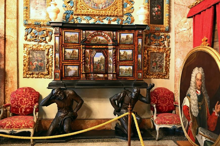 По обе  стороны от трона красивые и необычные секретеры, опирающиеся на человеческие фигуры.
