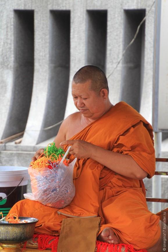 Монах то ли продавал, то ли раздавал что-то пестрое и явно полезное для кармы.