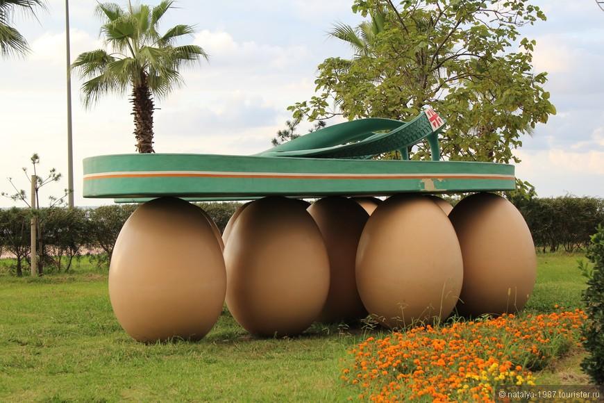 «Вьетнамки на яйцах». Так и не нашла информации, как правильно называется эта скульптура. Читала, что эта композиция – видоизменная работа художницы Лили Фантоцци, она посвятила её французской поговорке: «Пока живешь надо ходить так, будто ты шагаешь по яйцам». В оригинале были кеды, здесь их заменили на шлепанцы.