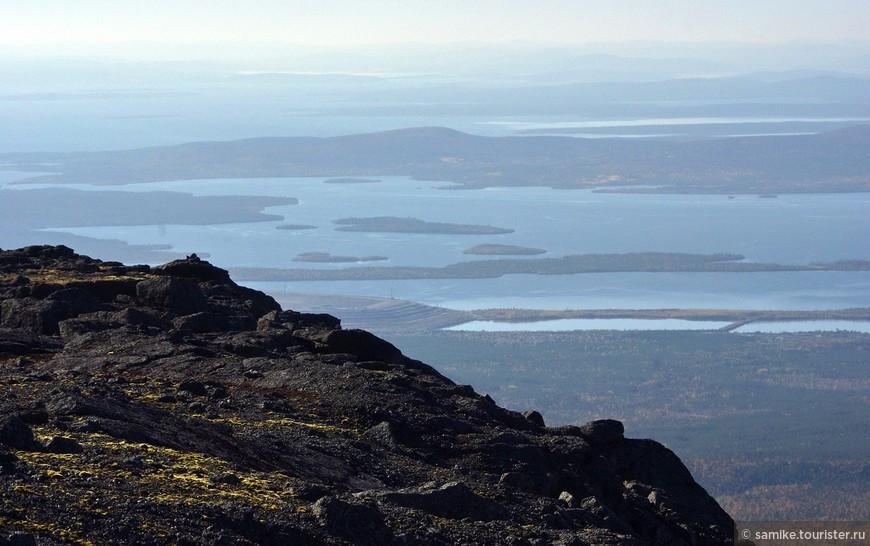 Расположившись лагерем у подножия горы Юдычвумчорр, мы конечно же не могли не покорить ее вершину :) Выходим из лагеря около одиннадцати утра и часа через полтора мы на плато. Вершины у Юдычвумчорр как таковой нет — многие горы в Хибинах имеют довольно плоские вершины — плато. Плато это абсолютно безжизненно — камни и камни, кое где слегка поросшие лишайниками. На фото: вид с плато в сторону Большой Имандры.