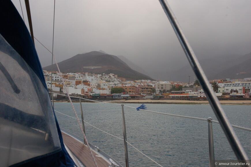 Поднявшись утром на палубу мы увидели туман, поднявшийся над островом. Шторм закончился и наша яхта мирно стояла на якоре. На берегу виднеются домишки последнего населённого пункта на Фуэртевентуре Эль Пуэртито де ла Крус.