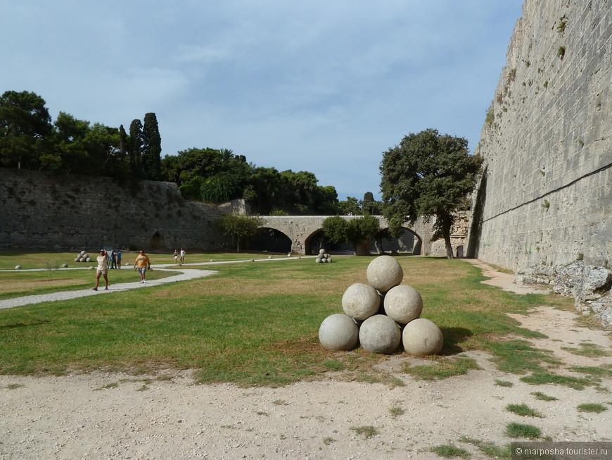 В старом городе Родос между крепостными стенами когда-то был ров, а сейчас это красивый ухоженный парк с дорожками и фигурно сложенными ядрами.
