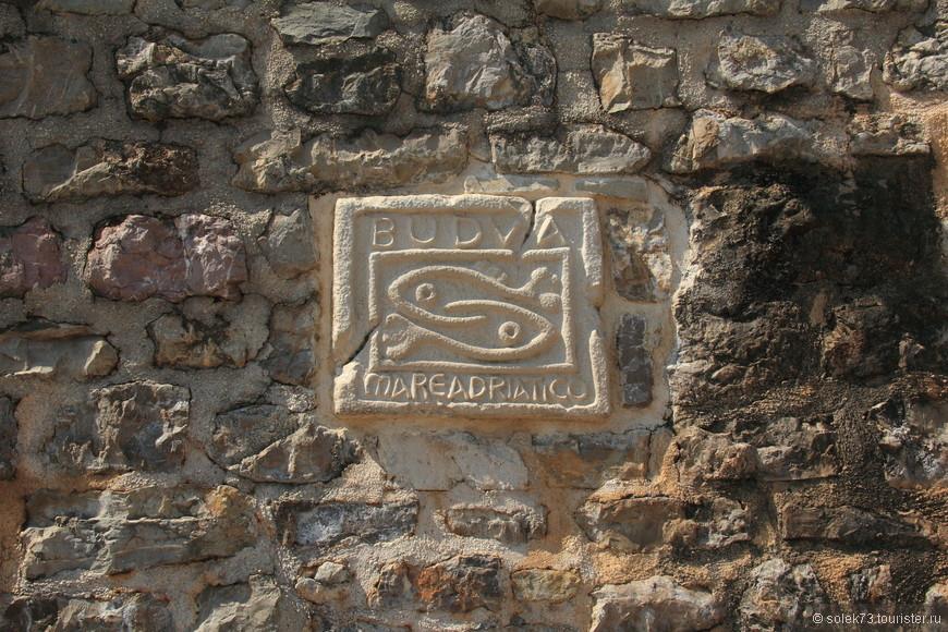 """Две неразлучные рыбки, похожие на знак """"инь и янь"""" являются символом города. Местная легенда гласит: бедный каменщик полюбил дочь богача ,но пожениться им не разрешали. Тогда несчастные влюблённые со словами """"Пусть двое будут как один"""" бросились с городской стены в море и превратились в рыб"""