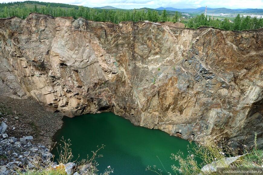 Это техногенный провал на месте закрытого в 1954 году подземного рудника недалеко от п.Туим. Изначально отрабатывались вольфрамовые руды, позже были выявлены медно-молибденовые. Месторождение отрабатывалось подземным способом. В результате взрывных работ кровля рудника проседала и позже обрушилась, образовав техногенную депрессию. Руду вывозили вагонетками наружу, а затем отправляли на обогатительную фабрику, расположенную на окраине п.Туим. Вырабатывали вольфрам, медь, молибден. После консервации рудника на вершине горы в результате обвала подземных горных выработок образовалась впадина диаметром 6 м, которая постоянно расширялась. На дне образовалось озеро с водой, окрашенной в ярко-голубой цвет. В настоящее время его диаметр достигает 200 м. От вершины горы до уровня воды 120 м (Википедия).