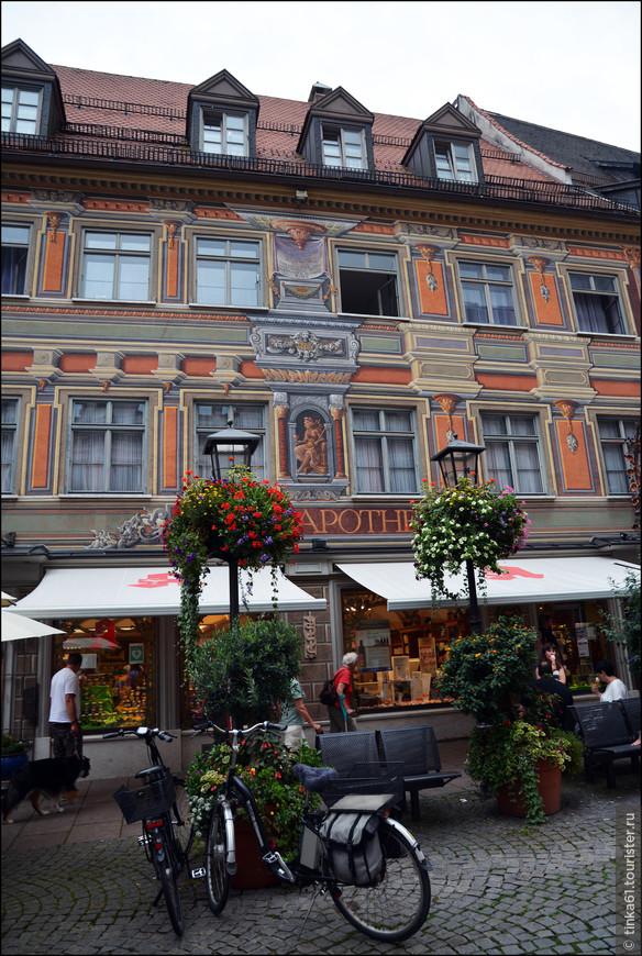 Нарядный фасад этого дома сразу же привлекает к себе внимание. Вся красота этого дома нарисована на фасаде, это национальная баварская традиция таким образом украшать здания. Фасад абсолютно ровный и плоский, все объёмные барочные декорации изображены при помощи красок.