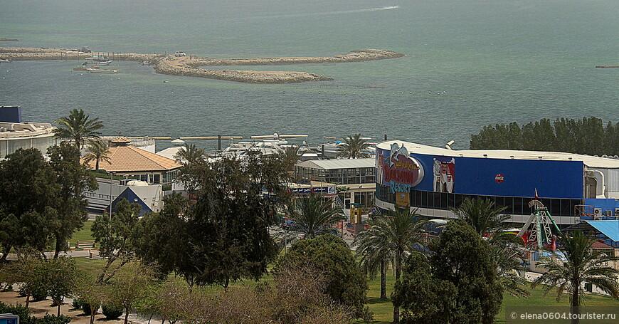 """Дельфинарий Манамы (Dolphin Resort - здание с синей крышей) располагается на набережной Аль Фатих, на территории парка """"Марина Гарден"""", который является одним из лучших мест столицы Бахрейна для отдыха всей семьей. Посетители дельфинария имеют возможность увидеть увлекательное представление в воде с участием дельфинов и морских котиков. Дети могут даже поучаствовать в шоу. Разрешена съемка с животными, участвующими в представлении. Кроме дельфинария, на территории парка есть аттракционы и несколько кафе, в которых можно перекусить и отдохнуть."""