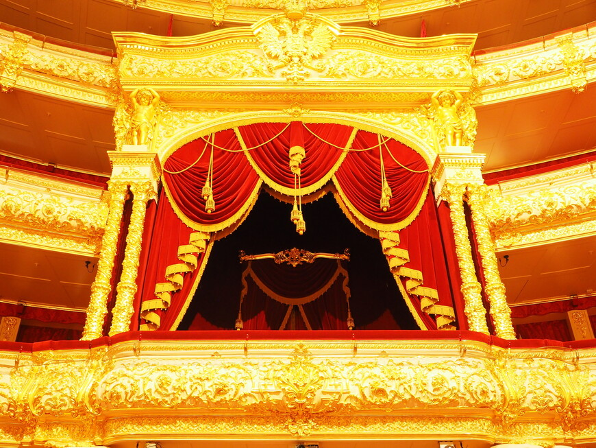 Вид на царскую ложу, самое богато украшенное место в театре. От обилия золота рябит в глазах. Над ложей герб Российской империи.