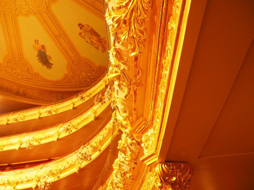 Золотой декор зрительного зала. Лепные украшения лож и ярусов театра из папье-маше или как еще их называли – арабески, были созданы в 1856 году, когда здание было восстановлено после пожара. Папье-маше, подобно дереву, имеет целлюлозную основу и обеспечивает хорошее звукоотражение, поэтому его использование наряду с резонансной елью и созданием формы зрительного зала в виде скрипки составляло одну из тайн акустики Большого театра. Реставрация архитектурного декора из папье-маше в зрительном зале было очень сложной процедурой, она включала расчистку и восстановление недостающих и утраченных частей декора по технологиям 19 веков. Еще более сложной процедурой было полиментное золочение, которое является одним из самых дорогих и сложных технологий золочения. Однако декоративный эффект получаемого золочения превосходит все остальные, поскольку золото полируется, и достигается максимальный его блеск. В реставрации позолоты декора зрительного зала принимало участие более 150 позолотчиков-полиментщиков, которых собирали со всей страны. Для золочения декора зрительного зала потребовалось почти 5кГ сусального золота и ушло 2,8 тысячи книжек сусального золота 960-й пробы. Технология золочения на полимент чрезвычайно сложная, требующая огромного терпения, навыка и опыта, настоящих мастеров по стране также мало как летчиков стратегической авиации. Достаточно вспомнить, что стандартная толщина листа сусального золота равна от 0,1 до 0,25 микрона или в миллиметрах (1мм = 1000микрон) от 0,0001 до 0,00025мм и малейшее дуновение ветерка уносит лист сусального золота как пушинку.