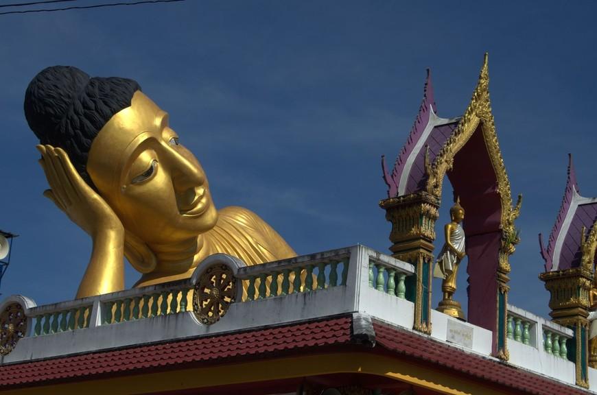 А знаете ли вы, что на Пхукете есть гигантская статуя лежащего Будды? Большинство гостей острова даже не подозревают о существовании подобного храма, незаслуженно обходя его стороной. Среди местных жителей храм ещё известен под названием Ват Липон (Wat Lipon). Он находится в районе Таланг, недалеко от памятника Героиням Пхукета и Музея Таланга.