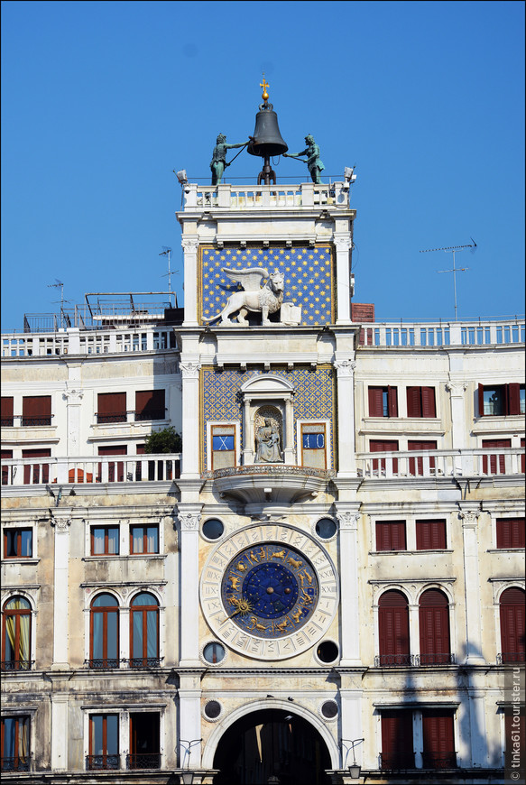 Вид на Torre dell orologio  c площади Святого Марка. Часовая башня увенчана  колоколом, по которому каждый час бьют бронзовые статуи, а циферблат украшен знаками зодиака.