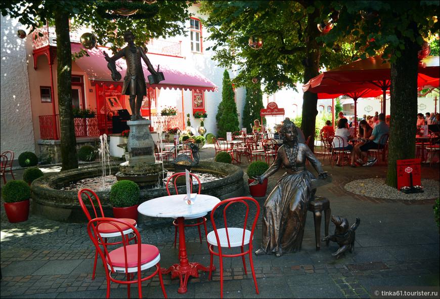 Фонтан Моцарту перед кондитерской. На редкость уютное местечко.Маленькие столики расположены в маленьком дворике, где все дополнено декоративными мелочами. Воздух наполнен приятным  ароматом кофе и шоколада. Все декоративные элементы выполнены в красных тонах и дополнены золотом. Пройти мимо невозможно.