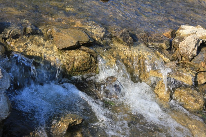 Чистая вода из водопадной чаши перетекает в ручей.