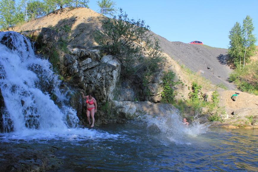 Купальщики: женщина идёт к водопаду,мужчина только что прыгнул(нырнул).