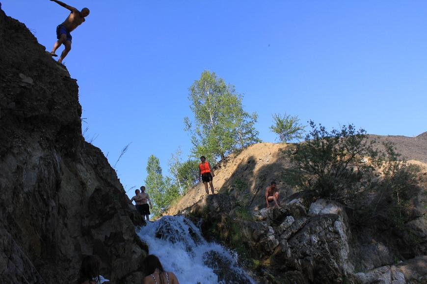 Ныряльщик прыгает с вершины водопада.