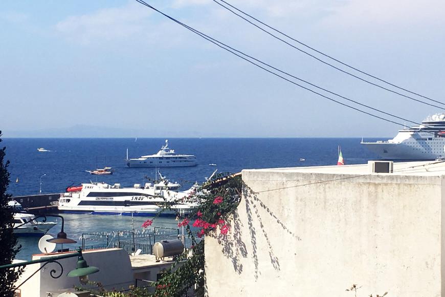 """о. Капри, вид изнутри. Синее море, белые стены, розовые цветы. Идеальное сочетание для эстетов! Прибывая на остров, туристы непременно направляются в Grota Azzurra. Мы таким образом потеряли целый день, так как сначала пропускали толпу """"первопроходцев"""", а после на море поднялись волны, и туристов в грот не возят! Выбирайте идеальный день, когда штиль, а лучше просто исследуйте остров"""