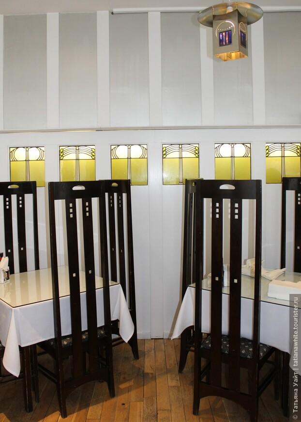Детали интерьера: столы, стулья с вытянутой спинкой, витражные вкрамления с текучим дизайном, светильнк - всё это обязательные элементы гармоничного ансамьля гениального Чарльза Ренни Макинтоша.