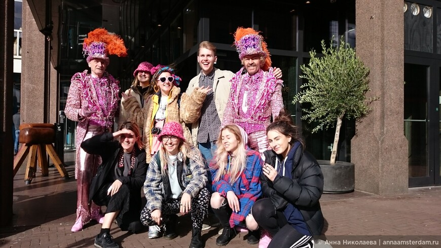 Два джентельмена в розовых костюмах, в прекрасный весенний солнечный день, развлекаются тем, что развлекают публику на улицах Амстердама, эпатажно прогуливаясь по центральным улицам и площадям и благодушно позволяя с собой фотографироваться. Туристы думают, что им очень повезло сделать уникальное фото с розовыми джентельменами. А на самом деле джентельмены-эгзибиционисты специально прогуливаются и получают от внимания большое удовольствие ;) Удивительное совпадение, что у двоих из туристок тоже розовые шапочки, двойной восторг! :D