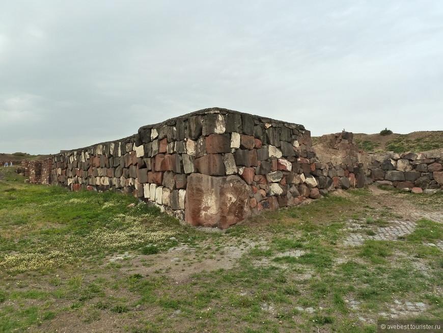 """Внешняя крепостная стена состояла из сложенного из базальтовых камней (иногда в качестве камней фундамента использовался также туф) цоколя высотой 2 метра и стены, сложенной из кирпича-сырца, высотой около 7 метров. Крепостная стена была усилена через каждые 8 метров контрфорсами пятиметровой ширины. В некоторых местах общая высота стен достигала 12 метров. Для скрепления камней и сырцового кирпича использовался глиняный раствор. Вокруг крепостных стен с внешней стороны была сделана отмостка, дополнительно укрепляющая фундамент и позволяющая охранникам делать обходы крепости. <noindex><noindex><a href=""""https://www.tourister.ru/go?url=https://www.smileplanet.ru/armenia/erevan/krepost-erebuni/"""" class=""""ext_link"""" target=""""_blank"""">https://www.smileplanet.ru/...</a></noindex></noindex>"""