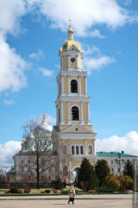 """Пятиярусная колокольня была построена в  1903 году по проекту архитектора А.К. Никитина. Это высотная доминанта монастыря —70,3 м. С севера и юга от проездной арки, которая одновременно является главным входом в монастырь, расположены два трёхэтажных корпуса — так называемые """"Рукодельный"""" и """"Иконописный"""". На третьем и четвёртом ярусах размещены колокола, на верхнем, пятом, – часовой механизм."""