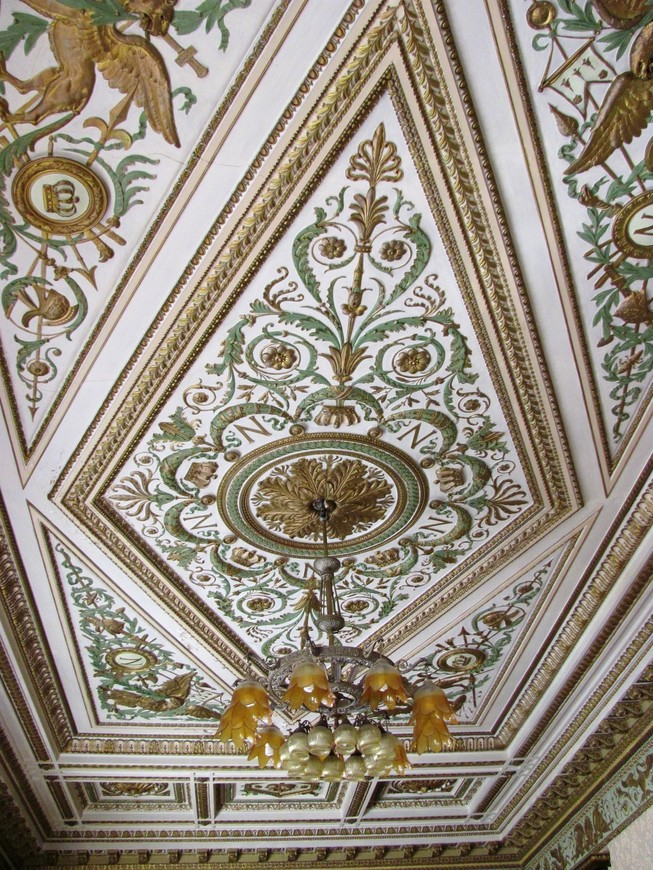 Шикарный потолок большого зала сохранился, но общий вид нарушает странная люстра.
