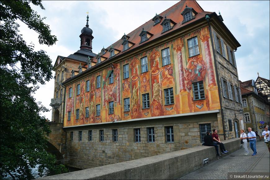 Старая Ратуша, одно из самых важных исторических зданий Бамберга. Расположена в самом центре Старого города, посередине крохотного искусственного островка на реке Регниц, соединенного с сушей двумя мостами – Верхним (Obere Brücke) и Нижним (Untere Brücke). Здесь вид на Ратушу со стороны Нижнего моста. Фрески на фасаде – своды, колонны и ниши – создают впечатление объемного изображения.