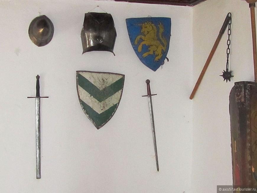 По стенам, как и положено, развешаны оружие, гербы...