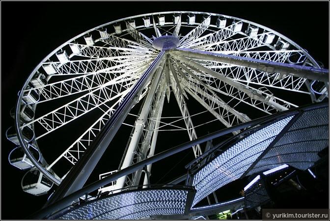 Ярким пятном на фоне ночного неба - колесо обозрения