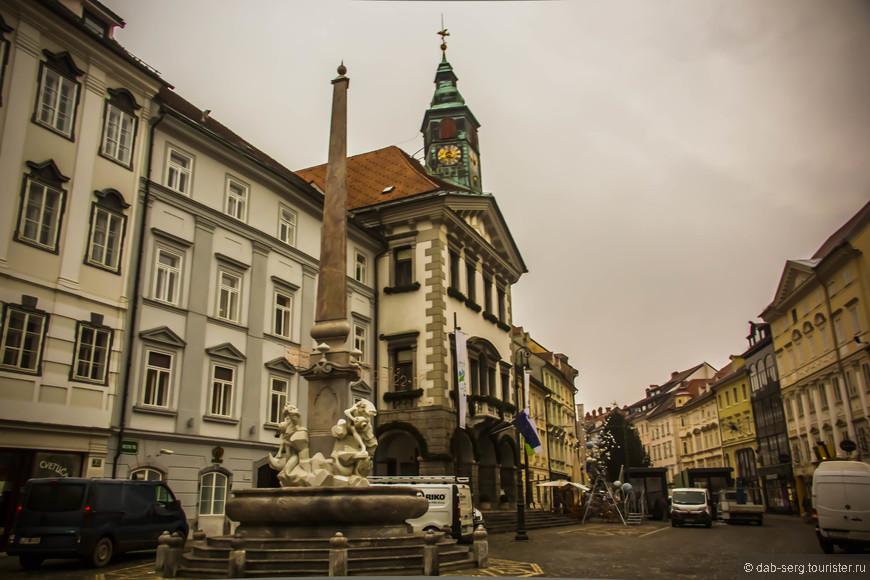 Фонтан трех рек Карниолии. Центр Старого Города. За ним здание мэрии города