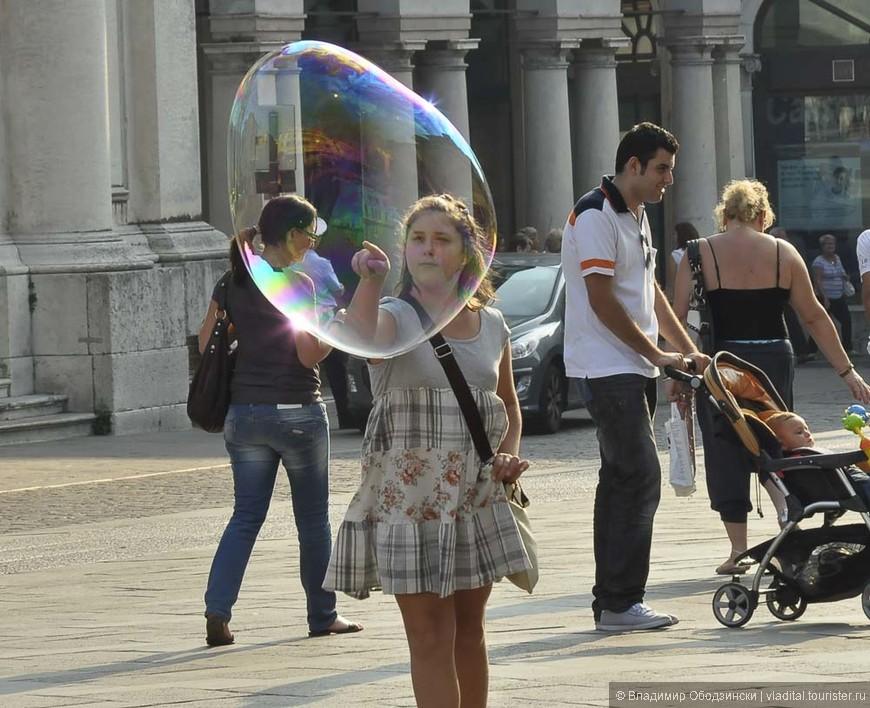 Эту девочку, так и не решившуюсь дотронуться до мыльного пузыря... я сфотографировал в Бассано дель Граппа. Она с удивлением проследила глазами за тем, как он проплыл мимо нее, чтобы торжественно лопнуть через несколько секунд.