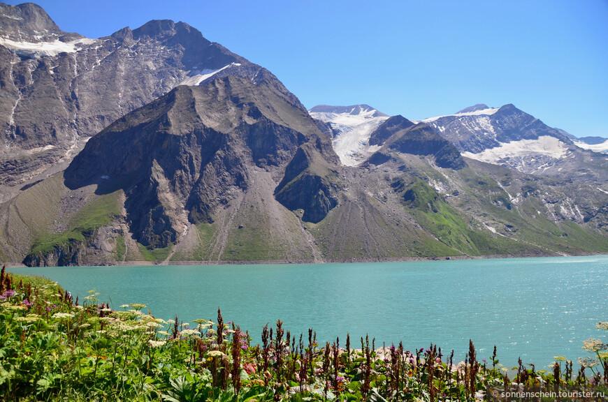 Наконец мы подъехали к конечной точки следования- верхнее водохранилище. Через несколько минут перед нами предстала такая картина. Заснеженные вершины, ручейки, с них стекающие, и бирюзовая вода водохранилища в окружении альпийских цветов.