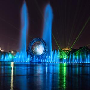 """Правый берег. Набережная реки Есиль рассвечивается лазерным шоу с музыкальным фонтаном """"Солнце"""" Конструкция фонтана выполнена в виде кольца, в центре которого создается водный """"экран"""", на котором проэцируется видео изображение. Фонтан впечатляет еще и своими размерами. Шоу проходит три раза за вечер. 21.00, 21.30, 22.00. Все они по сценарию и спецэффектам разные."""