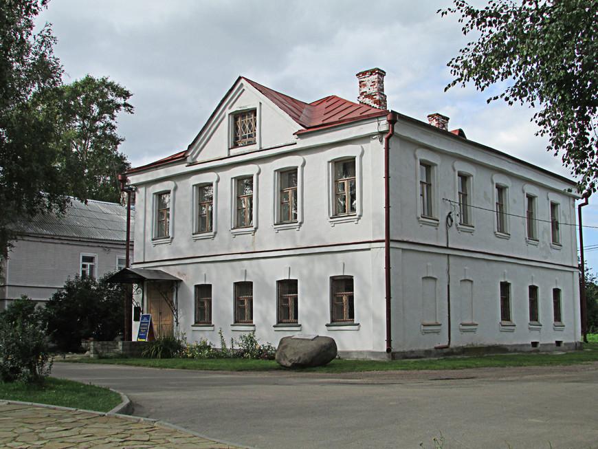 Напротив памятника находится дом купца Калязина, где теперь размещается Археологический музей Старой Ладоги.