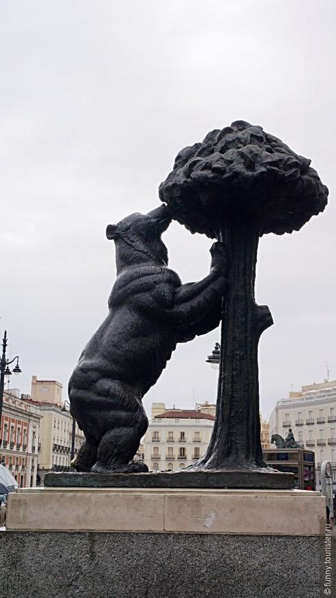 Этот символ – «медведь, тянущийся за плодами земляничного дерева» - восходит к традициям средневековья, когда медведь впервые стал использоваться на знаменах мадридских войск. Согласно историческим данным, в лесах под Мадридом в средневековье действительно водились медведи. В книге «Либро де Монтерия» король Альфонс XI свидетельствует о том, что Мадрид является хорошим местом для охоты на медведя и кабана. Точно неизвестно при этом с какого момента стали считать, что дерево на гербе «земляничное» (мадроньо, madroño). Дело в том, что изначально в Мадриде не росло земляничное дерево, его стали высаживать впоследствии по решению Правительства Мадрида именно потому, что оно является символом города. Ученые считают, что эта традиция могла пойти от того, что дерево, изображаемое с красными плодами, могло быть боярышником, виды которого растут в этом регионе.