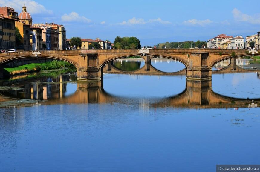 Мост Санта-Тринита великолепно смотрится с  Понте Веккьо. До 1557 года это был мост как мост - ничего особенного.  Но при наводнении  мост был снесен бурными потоками. Мост пришлось строить заново.Чтобы по нему было не стыдно устраивать шествие от  дворца Питти к  Санта-Мария-Новелла, правивший в то время герцог Козимо I, повелел построить  мост  с претензией на эстетику. Новый мост начал строиться в 1567 году, якобы по проекту  Микеланджело.