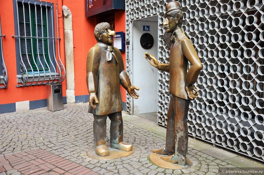 Толстый и тонкий, высокий и низкий, хитроумный и простой, городской и деревенский — скульптуры Тюннеса и Шеля в Кельне, знаменитых театральных героев и персонажей массы анекдотов, которые исполняют желания всех, кто сможет выполнить небольшой ритуал. Нужно всего-то наступить обоим на ноги, ухватить одного из них за нос и несколько секунд удержать равновесие