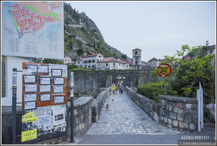 Один из входов в город - через перекинутый через канал мост. Слева на стенде - план старинного городка... И вновь эти самые объявления с потретами...