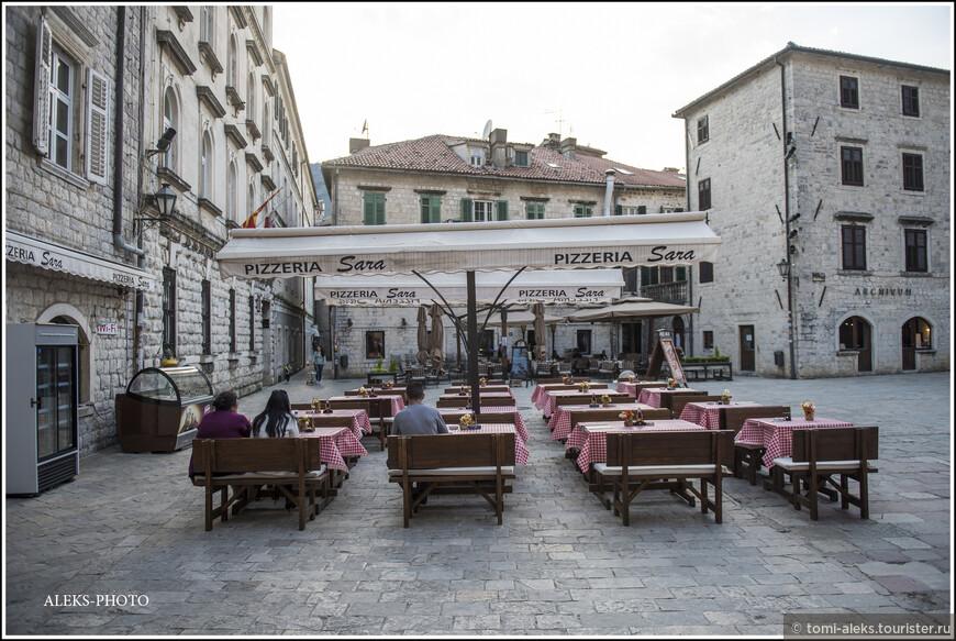 И пустые столики на такой же пустой площади...