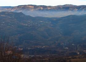 Мы подъезжаем к высокогорному городу Шуша. Внизу вид на равнину, на столицу Нагорного Карабаха Степанакерт. Зимой 1991–1992 годов Степанакерт подвергался обстрелам со стороны находившейся под азербайджанским контролем Шуши вплоть до её перехода под контроль вооружённых сил НКР 9 мая 1992 года. В результате этих обстрелов прямой наводкой со строны расположенной на высотах азербайджанской Шуши в низлежащем армянском Степанакерте не осталось не одного целого здания. В ночь с 8 на 9 мая 1992 года в ходе операции «Свадьба в горах» в город Шуши вошли арцахские войска. Азербайджанское население, составляющее основную часть Шуши вынуждено было бежать. Обстрелы Степанакерта, соотвественно, прекратились.