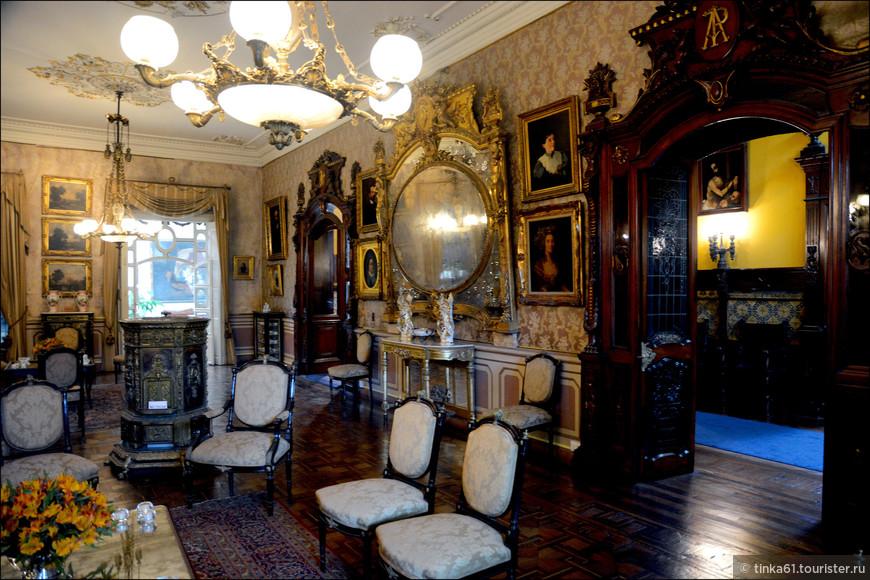Здесь мы видим множество картин, роскошное зеркало и элегантную мебель.