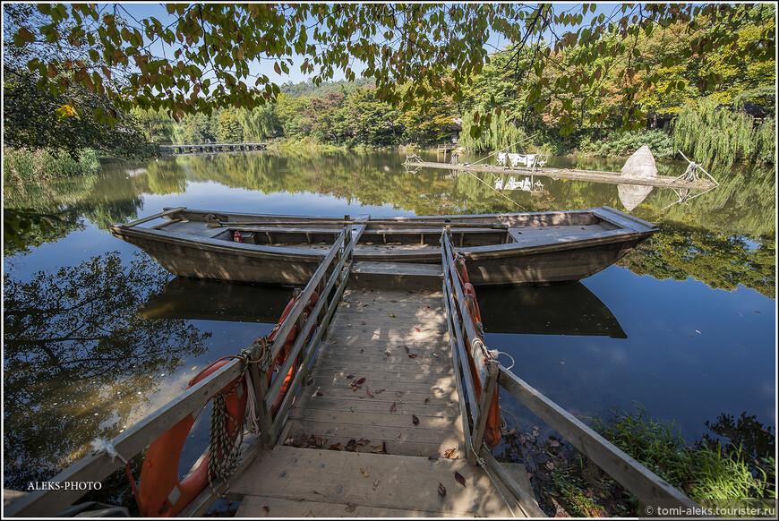 Мини-пристань со старинной лодкой.  На середине озера - какой-то маленький плавучий островок с шалашем. Такие артефакты заставляют пристально вглядываться в каждую деталь. В мегаполисе такого не увидеть...