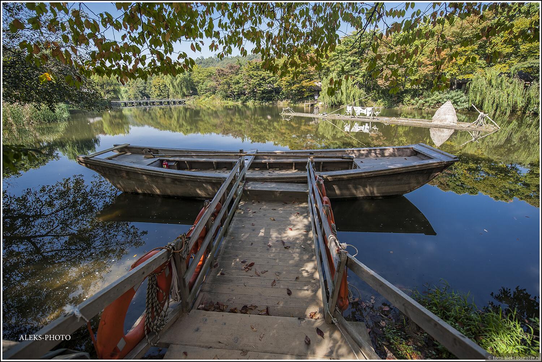 Мини-пристань со старинной лодкой.  На середине озера - какой-то маленький плавучий островок с шалашем. Такие артефакты заставляют пристально вглядываться в каждую деталь. В мегаполисе такого не увидеть..., Загадки корейской этно-деревни (часть первая)