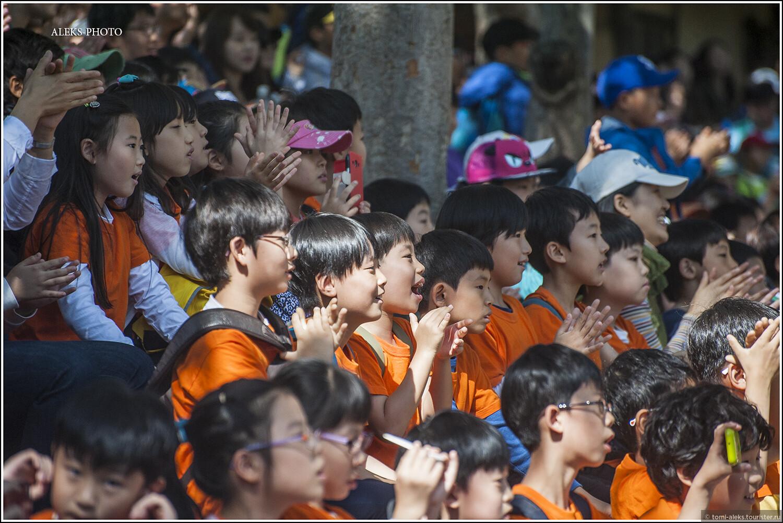 Многочисленная корейская детвора в восторге и рукоплещет... Удивляет организованность и дисциплина... Разные группы детишек одеты в майки разных цветов. Так их легче отличать в толпе, ведь сюда приезжают из множества школ страны..., Загадки корейской этно-деревни (часть первая)