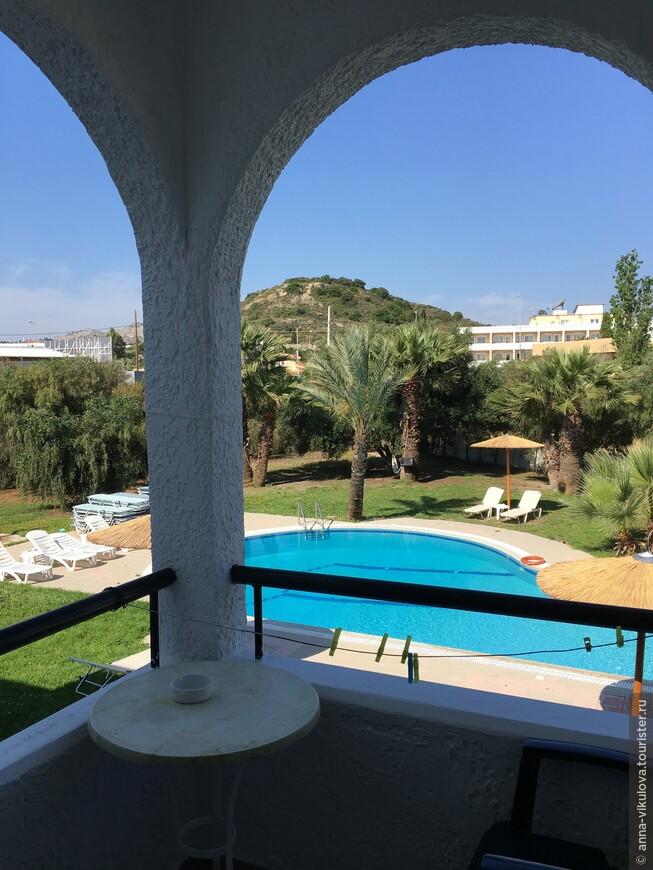 Вид с балкона на совсем небольшую, но уютную территорию отеля и бассейн.