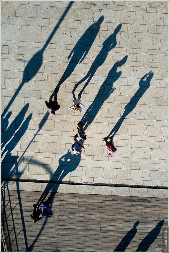 Тени людей на Cais da Ribeira. Фото с моста Луиша I. Порту.